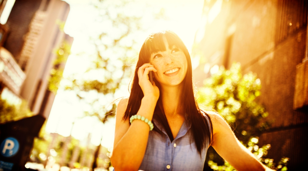 Woman talking on phone, walking down street